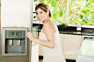 Frau steht vor Kühlschrank