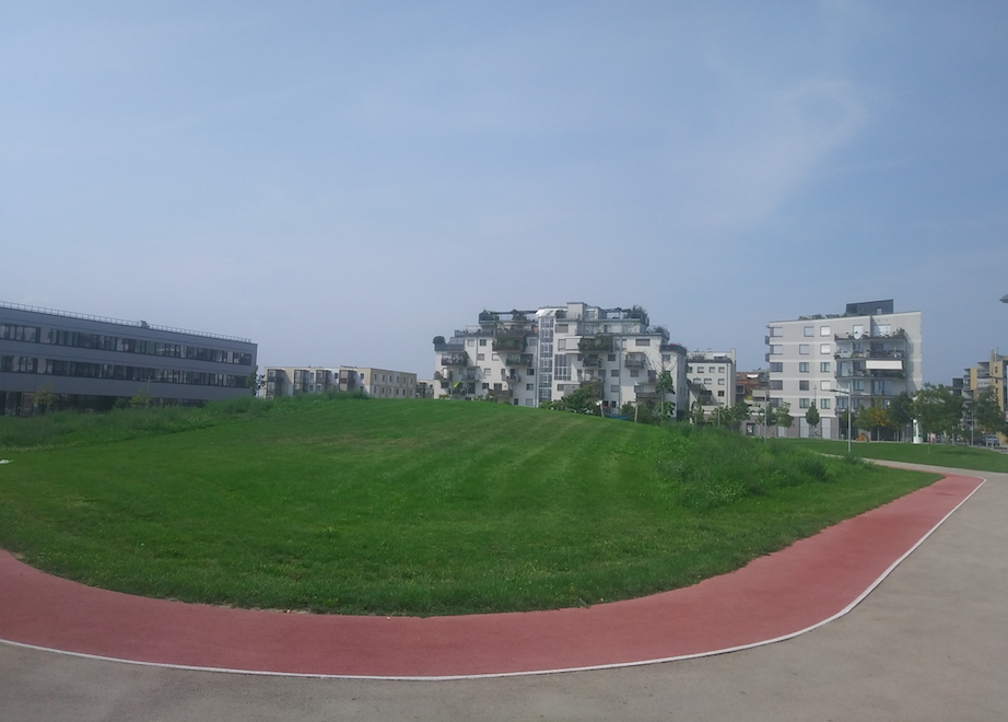 Laufbahn ums Grüne neben der Schule mit Blick auf die grünen Balkone eines Wohnhauses in der Seestadt