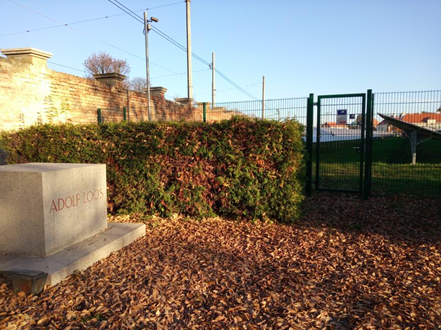 Das Grabmal von Adolf Loos wurde noch zu seinen Lebzeiten selbst von ihm entworfen. Unmittelbar daneben taucht ein grüner Zaun auf.