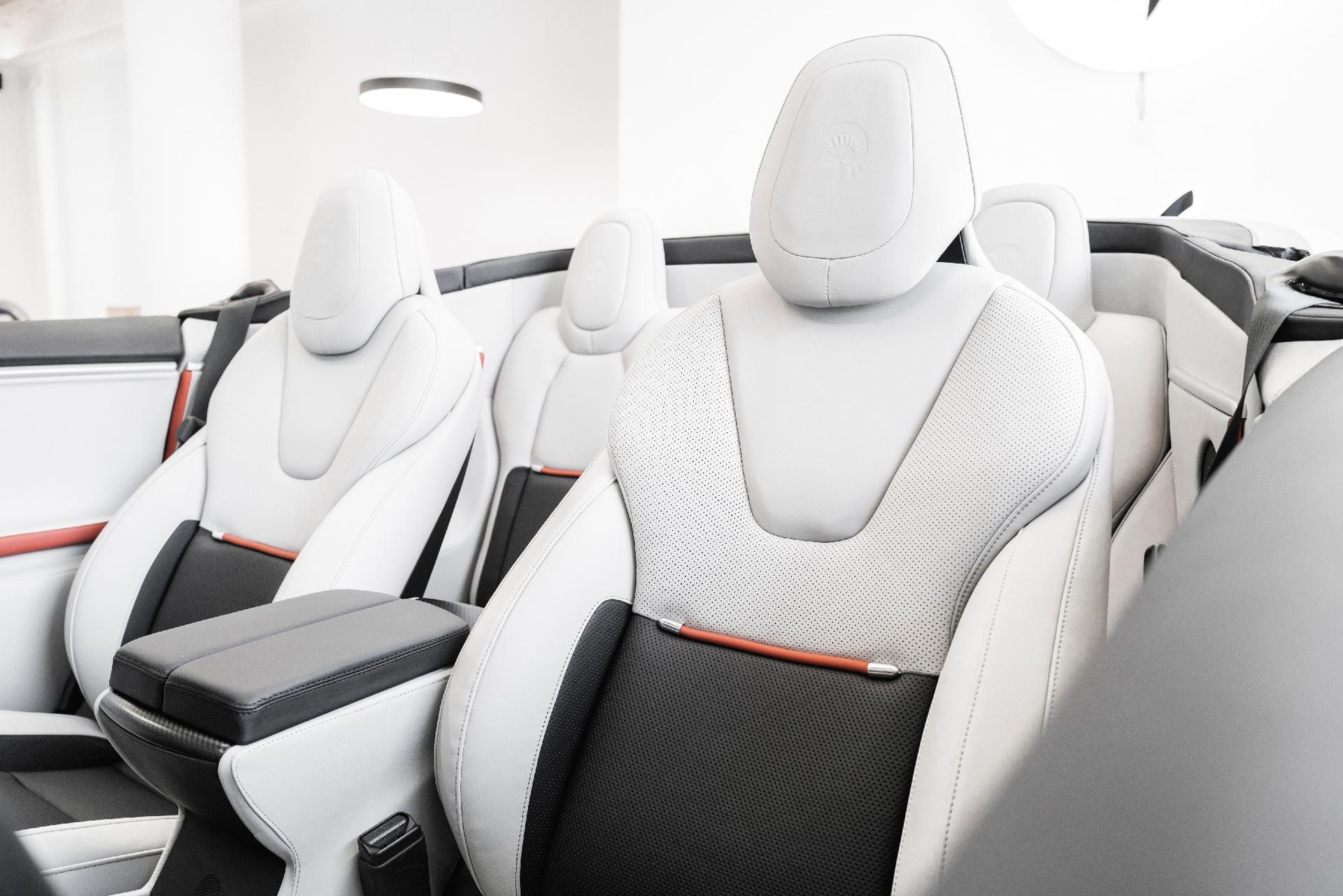 Eisweiße Ledersitze mit orangen Details wurden maßgeschneidert in das Tesla Cabrio eingebaut. Foto: ARES DESIGN – © www.aresdesign.com